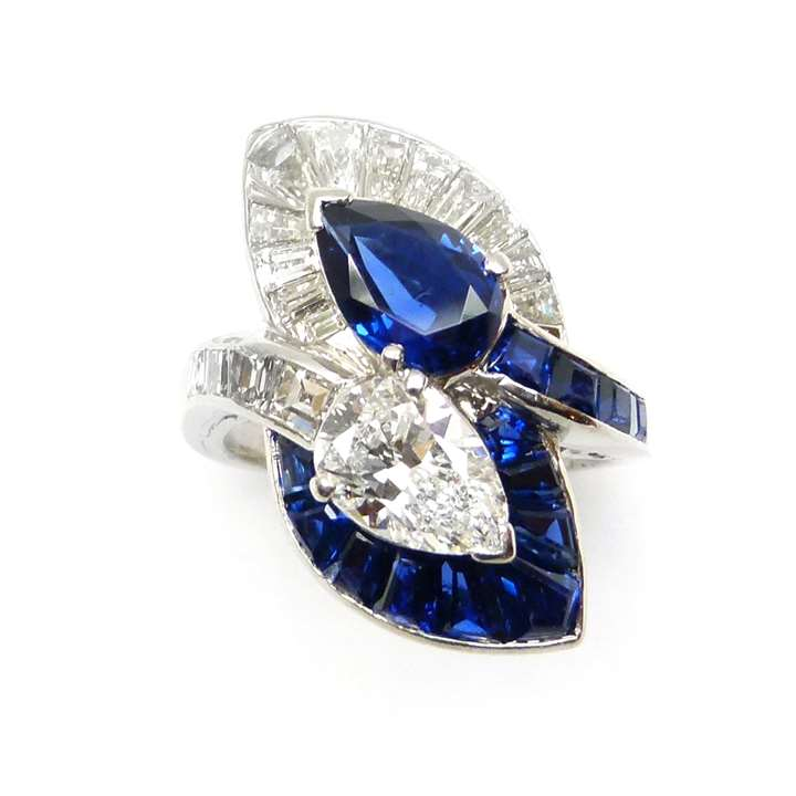 Two stone pear shaped sapphire and diamond crossover ring with leaf shaped clusters